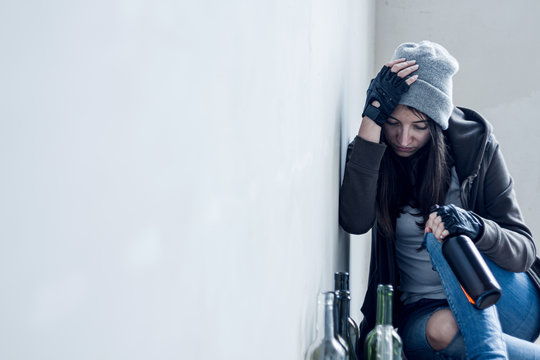 Homeless drunk young woman in hat is sitting on floor in abandoned building. Addicted teenage girl drunkard is drinking beer. Bum is living in street. Alcoholism, alcohol abuse concept.