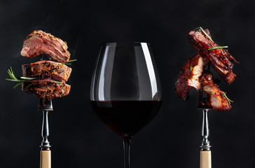 Foto op Plexiglas Wijn Red wine and grilled meat. Grilled pork belly and beef steak with rosemary on a black background.