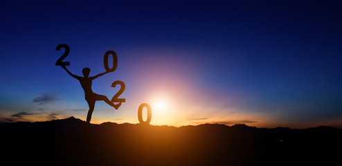 Silhouette of man doing walking on hill and 2020 years while celebrating new year at sunset background. Wall mural