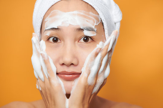 Beautiful Asian girl putting cream on her face. isolated on orange background.