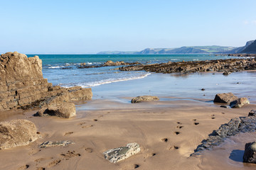 """Buck's Mills beach in North Devon, England. The gap in the rocks was man made and called """"The Gut"""" to create a harbour."""