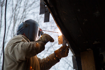 Welder working on the construction of the house.
