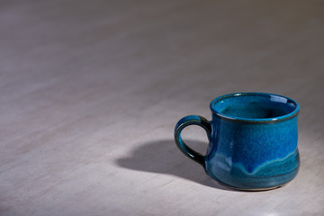 Blue handmade empty mug over grey background.