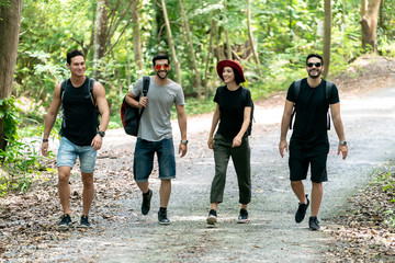 Group Of Friends hiking together through the forest