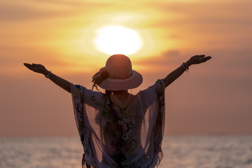 Middle Aged Women Hapy Lift their Arms out while the Sunset
