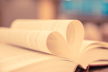 Close up book image in heart shape on the table at library room concept of lifestyle love to read.