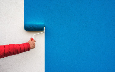 hand holds paint roller and painting a wall