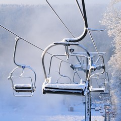 Chair lift for skiing covered in snow and hoarfrost at winter sunrise