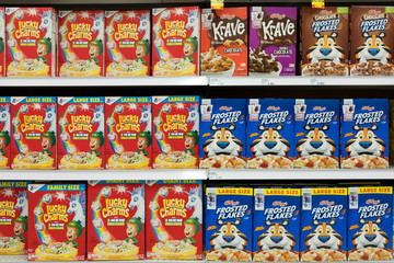 Grocery store shelf with boxes of various brands of breakfast cereal.