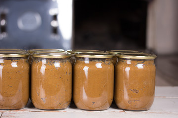 Cans of canned food are on the table, behind a wood-burning stove. Photo recipe