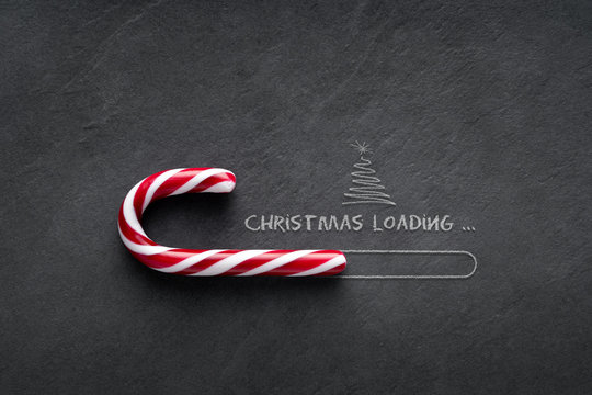 Christmas loading Concept - Candy cane on blackboard with christmas tree