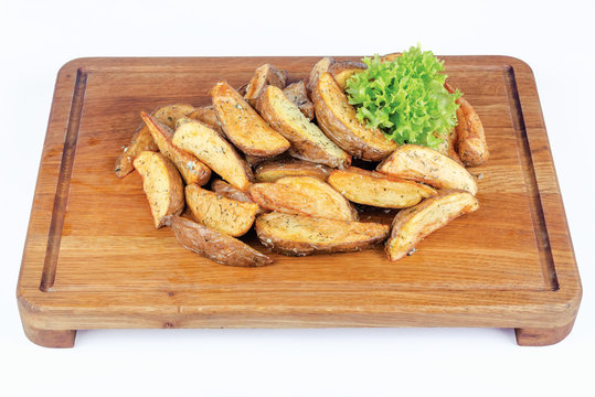 fried potato wedges or french fries or chips. home made in rural style on wooden board. healthy organic vegetarian food or beer snack