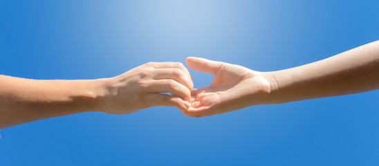 Helping hand concept. Gesture, a sign of help and hope. Two hands take each other. Against the background of blue sky banner.