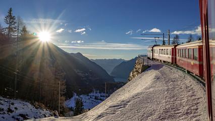 le train rouge glacier express traverse des paysages enneigés au soleil en suisse