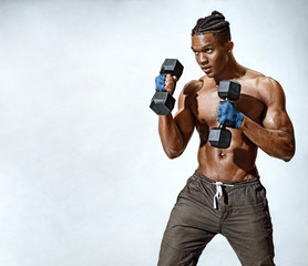Man in defensive stance. Photo of muscular man training with dumbbells on grey background. Strength and motivation