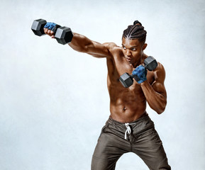 Man throwing a fierce and powerful punch. Photo of muscular man training with dumbbells on grey background. Strength and motivation