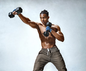 Sporty man making direct hit with dumbbells. Photo of muscular man doing boxing exercises on grey background. Strength and motivation