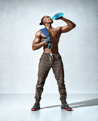 Man drinks water. Photo of sporty muscular man after hard workout on grey background. Resting time. Health concept.