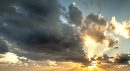 Dramatic sky with shining sun at sunset Wall mural