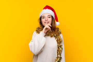 Girl with christmas hat over isolated yellow background doing silence gesture