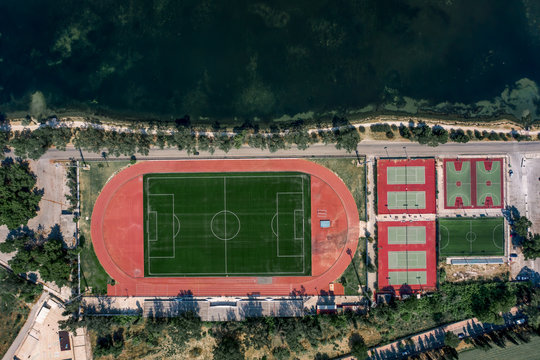 Aerial overhead drone shot of football field, tennis and basketball court in Argostolion, on Kefalonia Island