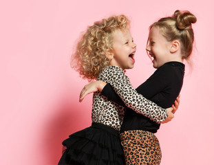 Two happy kids girls best friends sisters in leopard print clothes are hugging looking at each...