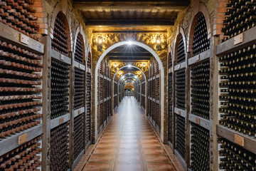 Autocollant pour porte Vin Wine bottles stacked up in underground wine cellar