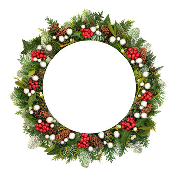 Christmas decorative table setting with round porcelain plate, silver bauble decorations &  winter greenery and holly on white background with copy space.
