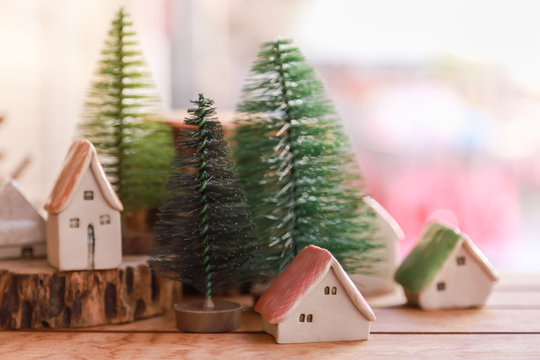 Winter, Autumn and Christmas and Holiday Season Concept. Close of miniature house figure and artificial pine xmas tree on wooden table.