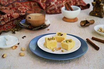Indian sweets with pistachios, almonds and cardamom on a white plate on a light concrete background. Served with masala tea. Traditional Indian sweets.