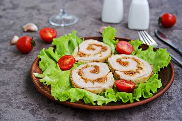 Cold appetizer, sliced baked pork roll with fried carrots and onions on fresh lettuce leaves on a clay plate on a gray concrete background. Holiday recipes meat dishes.