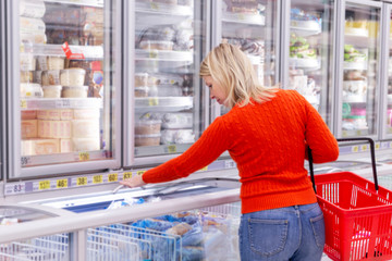 Young woman chooses frozen food in a supermarket.