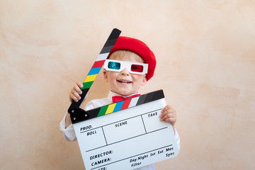 Funny kid holding clapper board