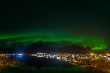 Reine fishing village with the northern lights, Aurora Borealis, mountains in the background, Lofoten Islands, Norway
