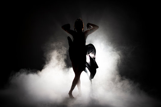 Silhouette dancer woman performing dance figures in fog.