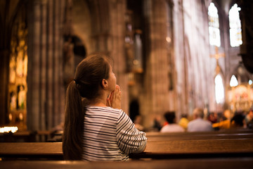 Young girl praying in church standing on her knees Fotomurales