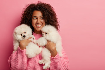 Positive curly female host happy to pose with two pedigree puppies, has good mood, smiles broadly,...