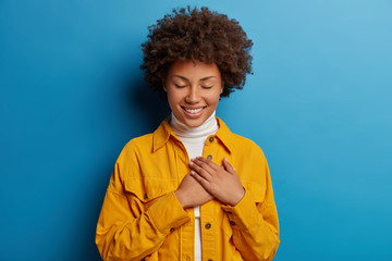 Tender feminine woman keeps hands on heart, has grateful look, appreciates effort, has eyes closed, wears yellow shirt, isolated over blue background, receives touching compliment, smiles pleasantly