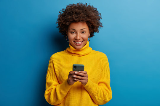 Photo of dark skinned lady enjoys distant communication, uses mobile phone, surfes fast unlimited internet, has pleasant smile, dressed in yellow sweater, makes shopping online, isolated on blue