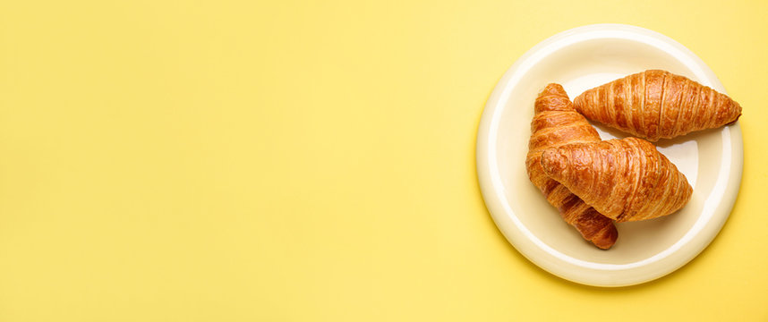 Plate with sweet croissants on color background with space for text