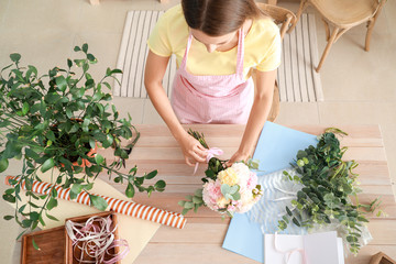 Female florist making beautiful bouquet in shop