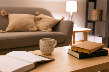 Books with cup of coffee on table in room at night Wall mural
