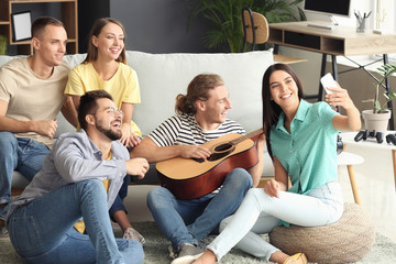 Group of friends taking selfie at home
