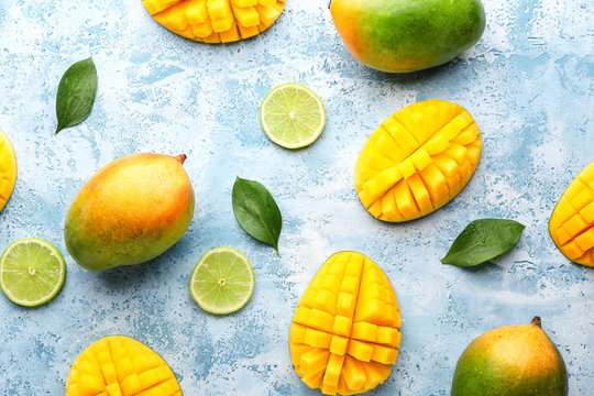 Sweet ripe mangoes and lime on color background