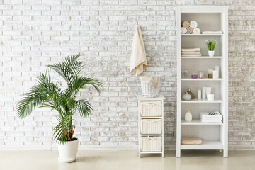 Shelf unit with towels and cosmetics near brick wall in bathroom