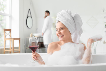 Fotomurales - Beautiful young woman drinking wine while taking bath