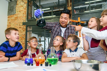 Pupils of primary school watch carefully for their teacher who shows interesting chemical...