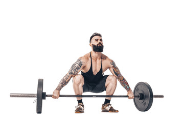 The technique of doing an exercise of deadlift with a barbell of a young muscular strong tattooed bearded sports men on a white studio background. Isolate