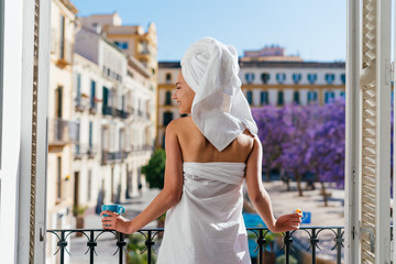 the hotel guest stands at the open window and looks out onto the street, a towel on her head, her body wrapped in a sheet, her back to the camera