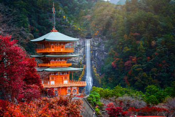 Stores photo Lieu de culte Kumano nachi taisha shrine with waterfalls along in view at season change of Autumn, the famous and popular tourist place in Kumano of Japan